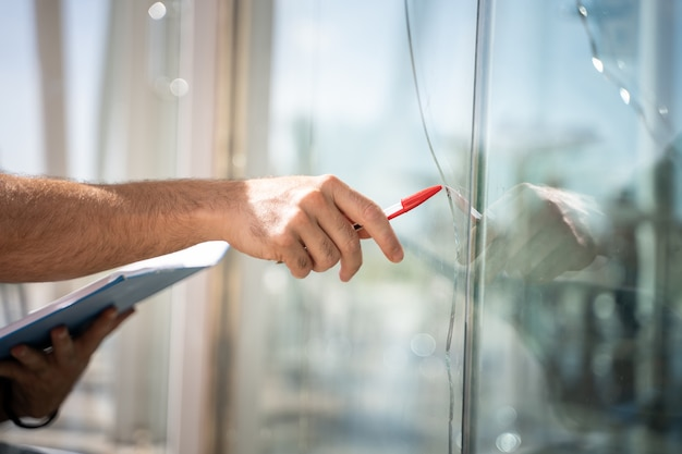 Vidrios rotos de una casa por un accidente, hombre revisando para reparar Foto gratis