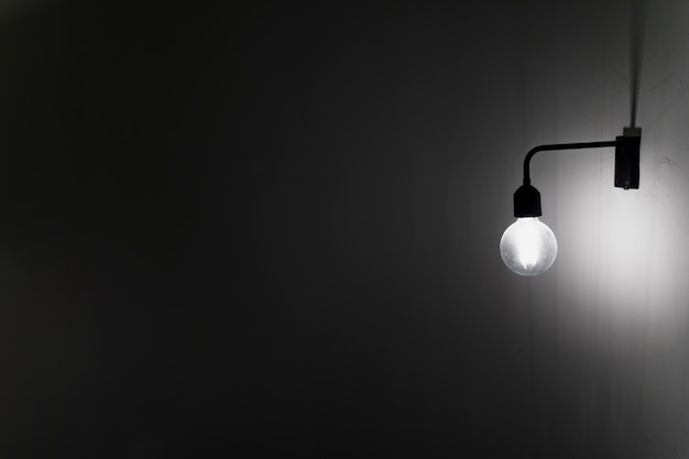 Una vieja bombilla en el muro de hormigón en la oscuridad Foto gratis