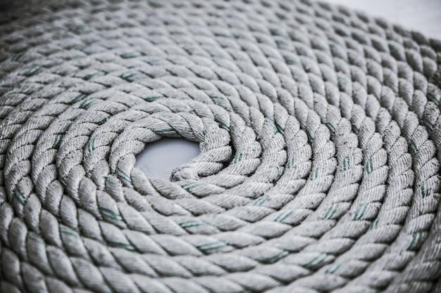 Vieja cuerda de amarre desgastada enrollada en un círculo Foto Premium
