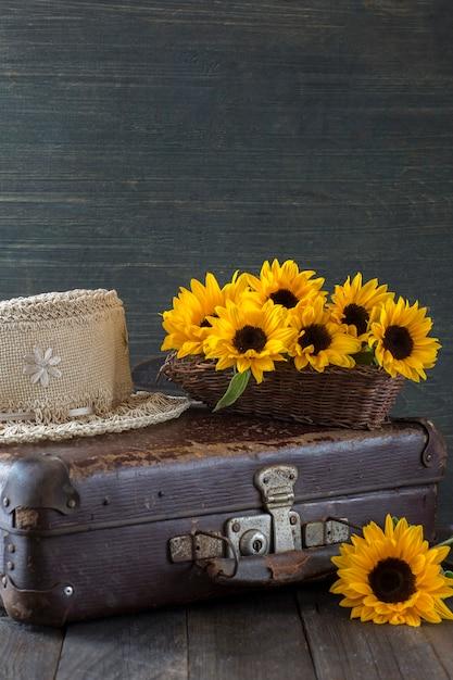 En una vieja maleta un ramo de girasoles y un sombrero de paja Foto Premium