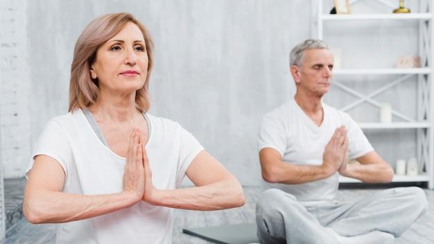 La vieja pareja sana que se sienta en actitud del loto con las manos de rogación Foto gratis
