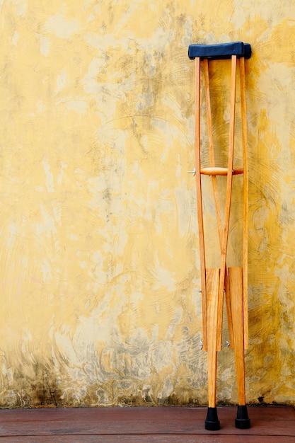 Las viejas muletas de madera se apoyan en la pared de cemento amarillo Foto Premium