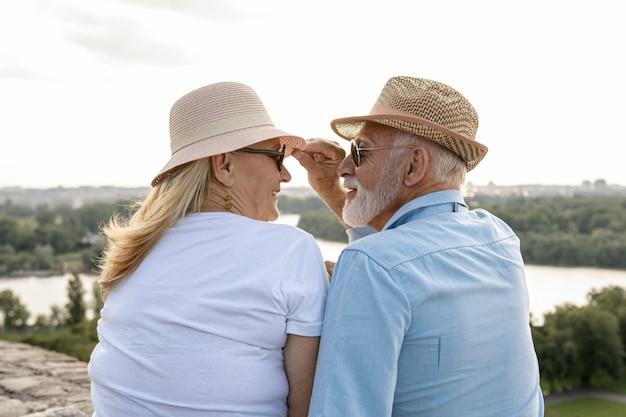 Viejo agarrando el sombrero de una mujer Foto gratis