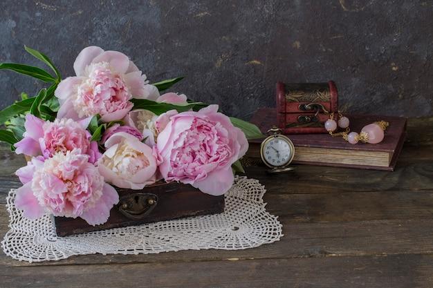 En un viejo cofre un ramo de peonías rosas, un libro, cuentas con piedras rosas. Foto Premium