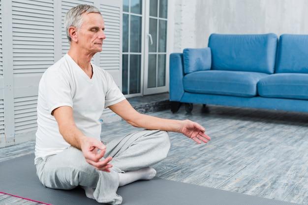 Viejo hombre concentrado que medita en la estera en casa Foto gratis