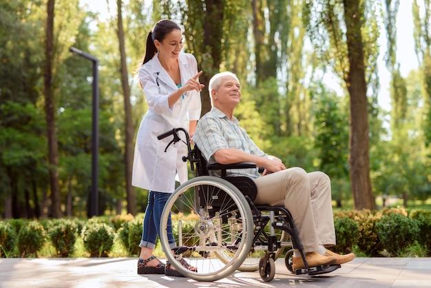 Viejo hombre feliz en silla de ruedas en parque con el doctor Foto Premium