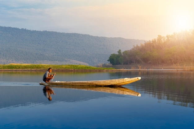 Viejo hombre pescando sentado en un bote de madera en un bote de madera en un lago en el lago Foto Premium