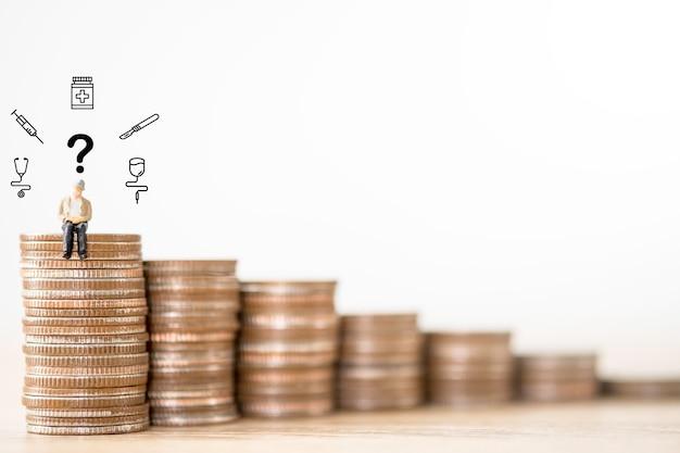 Viejo hombre sentado en monedas apilando con pregunta y elemento médico. concepto de selección de negocio de seguro de salud. Foto Premium