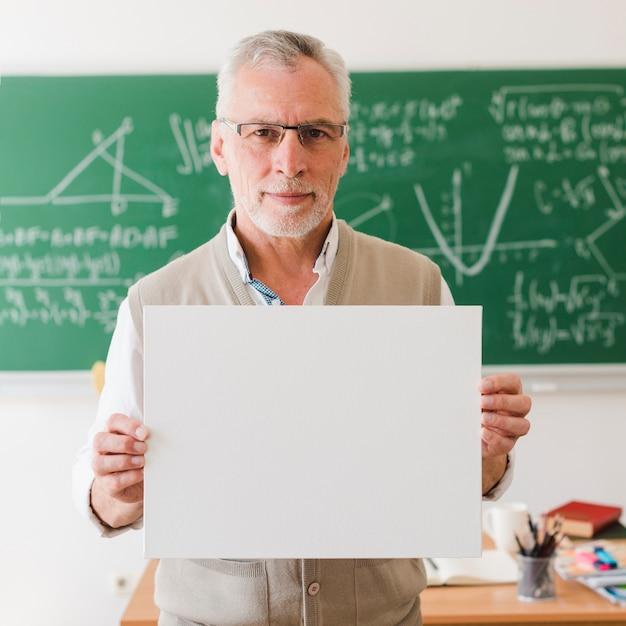Viejo maestro mostrando una hoja de papel transparente Foto gratis