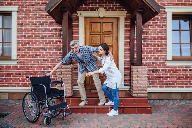 Viejo quiere sentarse en su silla de ruedas cerca de un hogar de ancianos Foto Premium