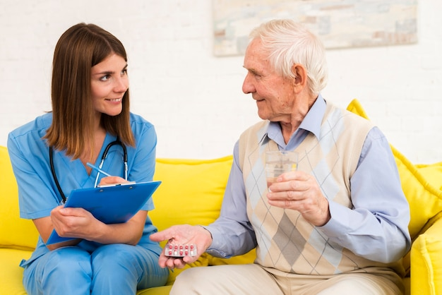 Viejo sosteniendo sus pastillas mientras hablaba con una enfermera Foto gratis