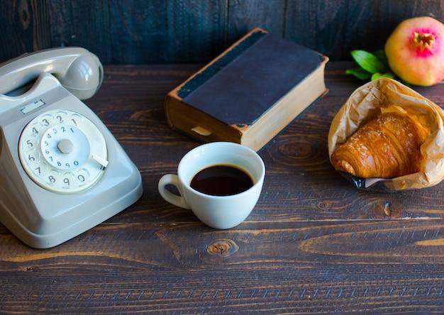 Viejo teléfono vintage, café, libro, sobre una superficie de madera Foto Premium