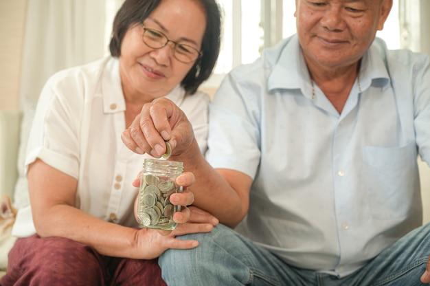 Viejos hombres y mujeres asiáticos se sientan en el sofá, hacen planes financieros. Foto Premium