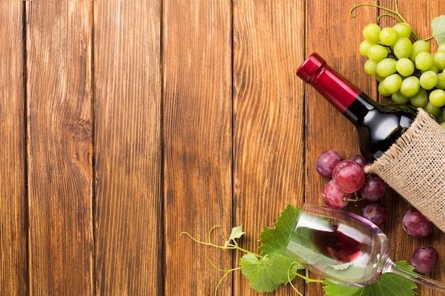 Vino con marco de uvas rojas y verdes. Foto gratis
