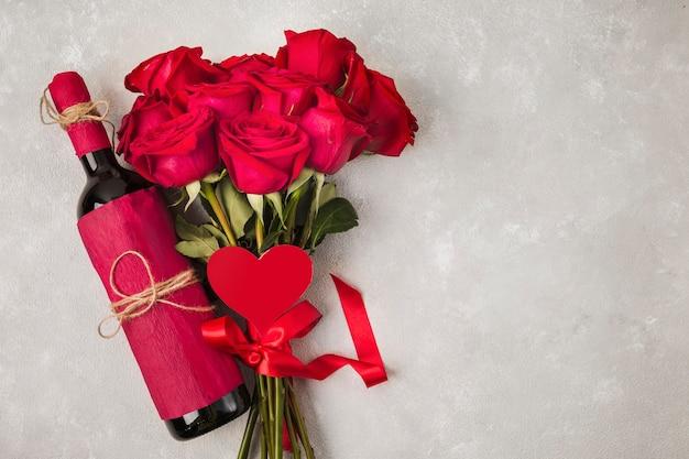 Vino ramo de rosas y brezo firman en mesa gris Foto gratis