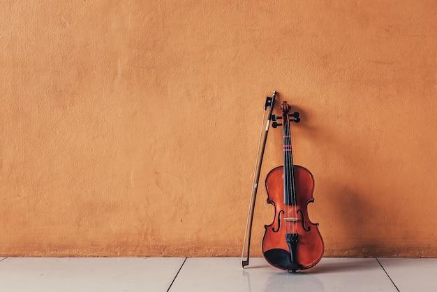Violín clásico antiguo puesto en paredes de cemento naranja Foto Premium