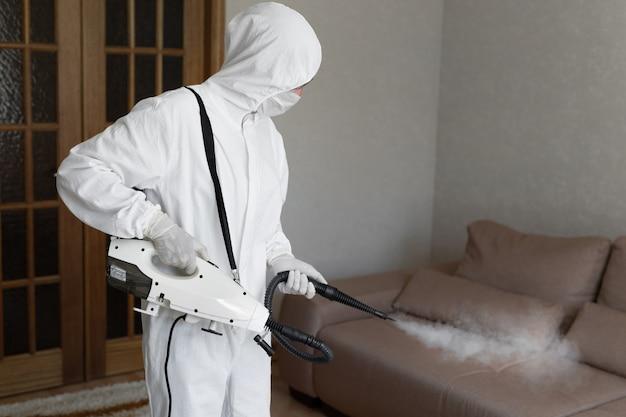 Virólogo en traje protector de materiales peligrosos realiza desinfecciones de superficies Foto Premium