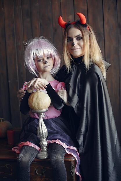 Víspera de todos los santos. madre e hija disfrazadas de halloween. familia en casa. Foto gratis