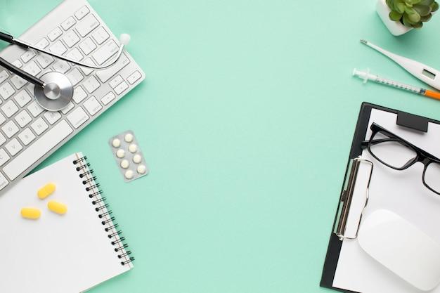 Vista de accesorios médicos y píldoras y planta pequeña en el escritorio del médico Foto gratis