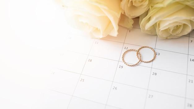 7e0408ddf37d Una vista aérea de los anillos de boda en la fecha del calendario con rosas