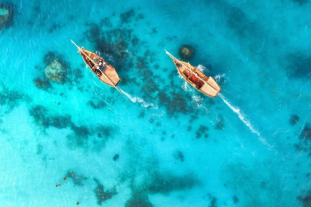 Vista aérea de los barcos de pesca en aguas cristalinas al atardecer en verano Foto Premium