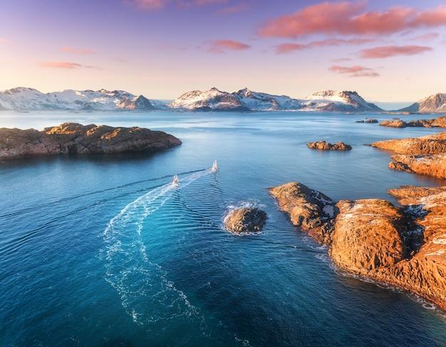Vista aérea de barcos de pesca, rocas en el mar azul, montañas nevadas y colorido cielo púrpura con nubes rojas al atardecer Foto Premium