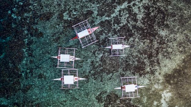 Vista aérea de los barcos tradicionales de filipinas en los arrecifes de coral Foto Premium