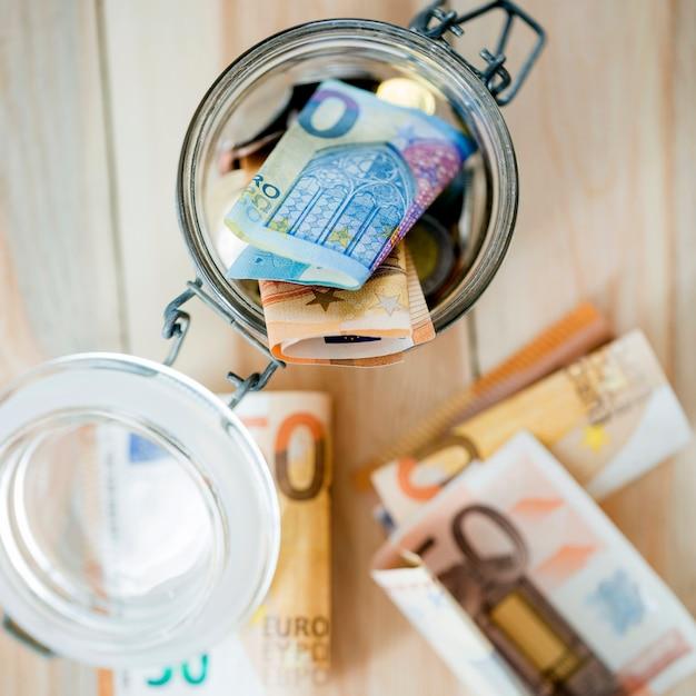 Una vista aérea de los billetes en euros en un frasco de vidrio abierto Foto gratis