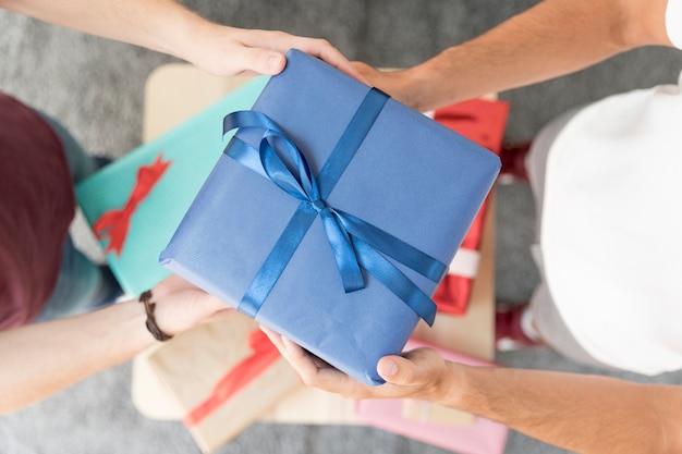 Vista aérea de la caja de regalo envuelta azul de la tenencia del amigo masculino con la cinta atada Foto gratis