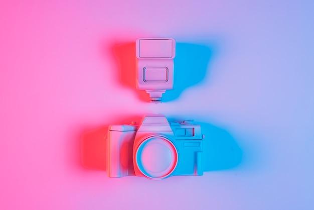 Vista aérea de la cámara rosa y lente con sombra y luz azul Foto gratis