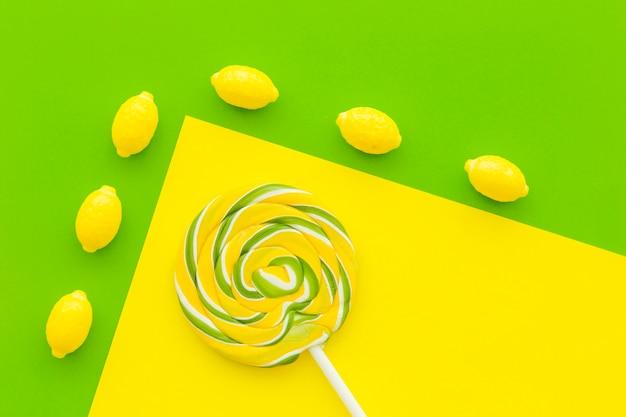 Vista aérea de caramelos de limón y piruleta en doble fondo amarillo y verde Foto gratis