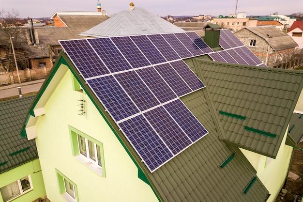 Vista aérea de la casa cabaña con azul brillante foto solar sistema de paneles voltaicos en el techo. producción ecológica renovable de energía verde. Foto Premium