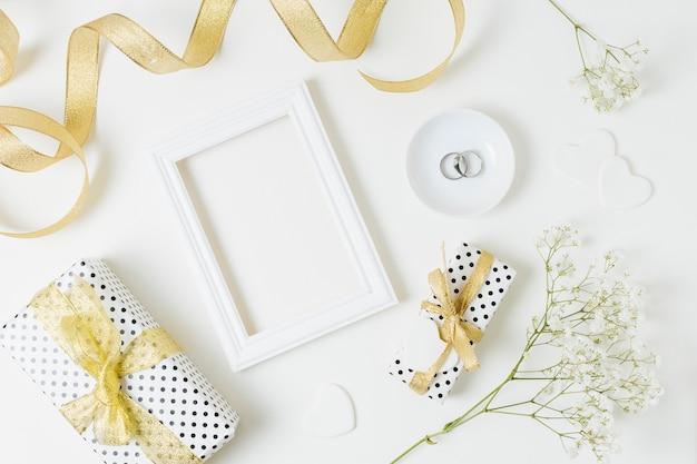 Una vista aérea de cinta dorada con cajas de regalo; cuadro; anillos de boda y flores de aliento de bebé sobre fondo blanco Foto gratis