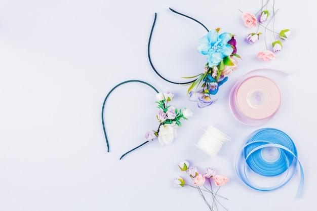 Una vista aérea de la cinta; flores artificiales; carrete para hacer hairbands sobre fondo blanco Foto gratis