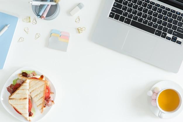 Vista aérea de la computadora portátil, sandwich fresco, taza de té verde y teléfono móvil en la mesa de escritorio blanco. concepto de negocio y desayuno de mujer, vista superior y endecha plana Foto Premium