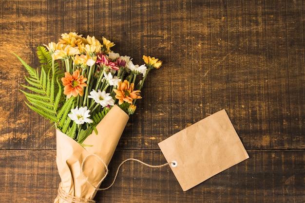 Vista aérea del delicado grupo de flores y la etiqueta de papel marrón en superficie de madera Foto gratis