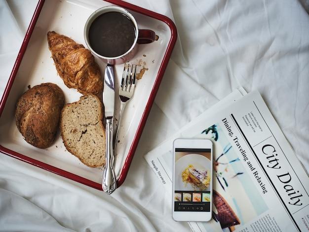 Vista aérea del desayuno café pan en bandeja en la cama Foto gratis