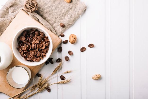 Vista aérea del desayuno con cereales de chocolate y leche en la mesa Foto gratis