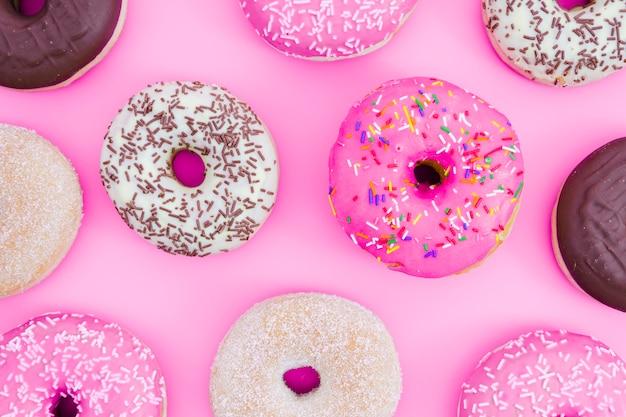 Una vista aérea de donuts sobre fondo rosa Foto gratis