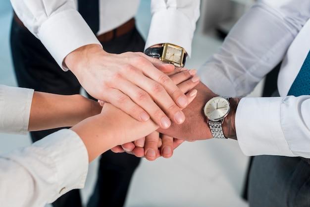 Una vista aérea del empresario y empresaria apilando las manos Foto gratis