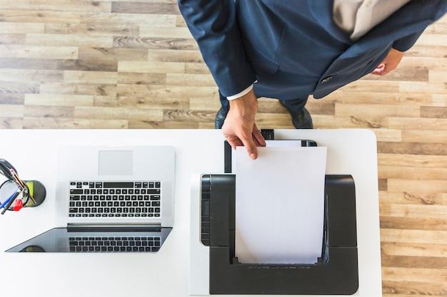 Una vista aérea del empresario que toma papel de la impresora en la oficina
