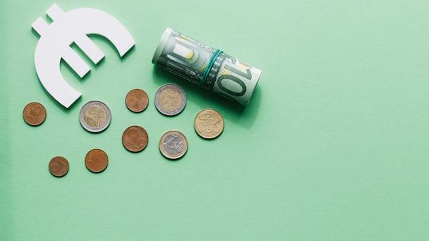 Vista aérea de enrollada nota de cien euros con símbolo y monedas en superficie verde Foto gratis