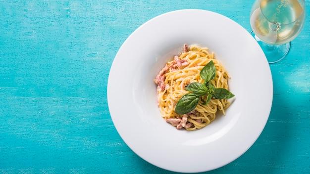 Una vista aérea de espaguetis con copa de vino sobre fondo turquesa Foto gratis