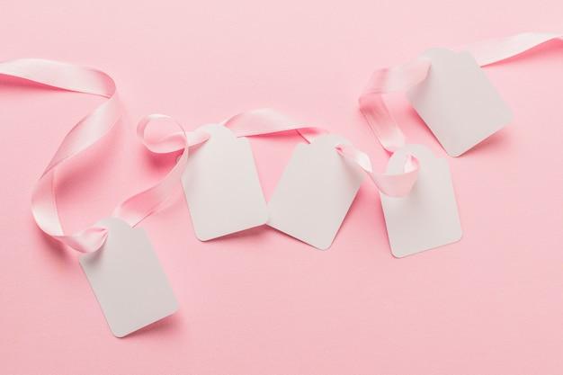 Vista aérea de etiquetas en blanco y cinta rosada contra un fondo rosado liso Foto gratis