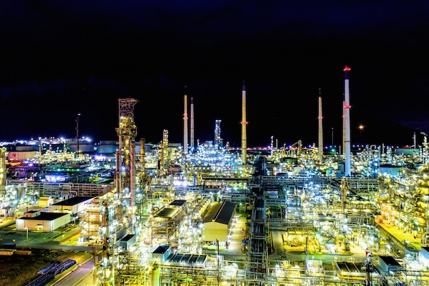 Vista aérea. fábrica de refinería de petróleo y tanque de almacenamiento de petróleo en la noche Foto Premium
