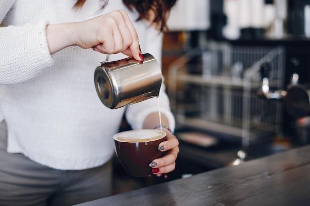 Vista aérea femenina barista vertiendo espuma de leche en capuchino en cafe Foto gratis