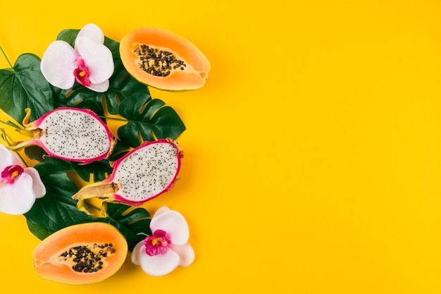 Una vista aérea de las frutas del dragón; papaya a la mitad con hojas y flor de orquídea sobre fondo amarillo Foto gratis