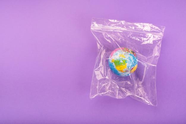 Vista aérea del globo en una bolsa de plástico con cierre hermético sobre fondo púrpura Foto gratis