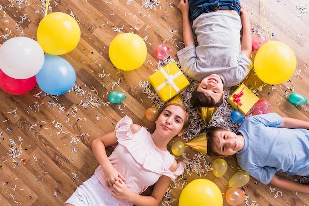 Vista aérea de hermanos felices tumbados con globos; caja de regalo y confeti en piso. Foto gratis