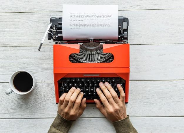 Vista aérea de un hombre escribiendo en una máquina de escribir retro Foto gratis